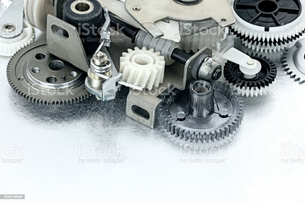 various cogwheels and other parts of industrial machinery on scratched background stock photo