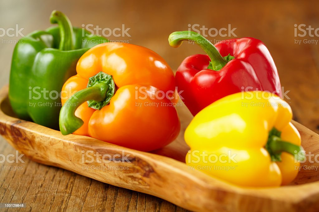 Various colorful bell peppers in wooden basket stock photo