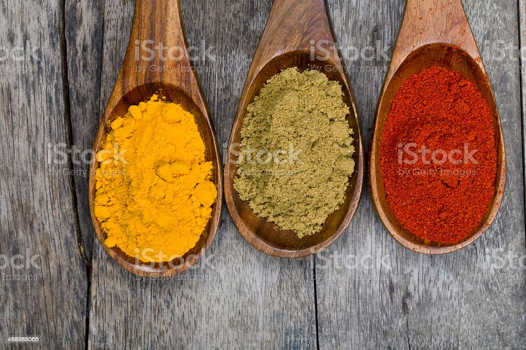 Various colorful spices in wooden spoons on table stock photo