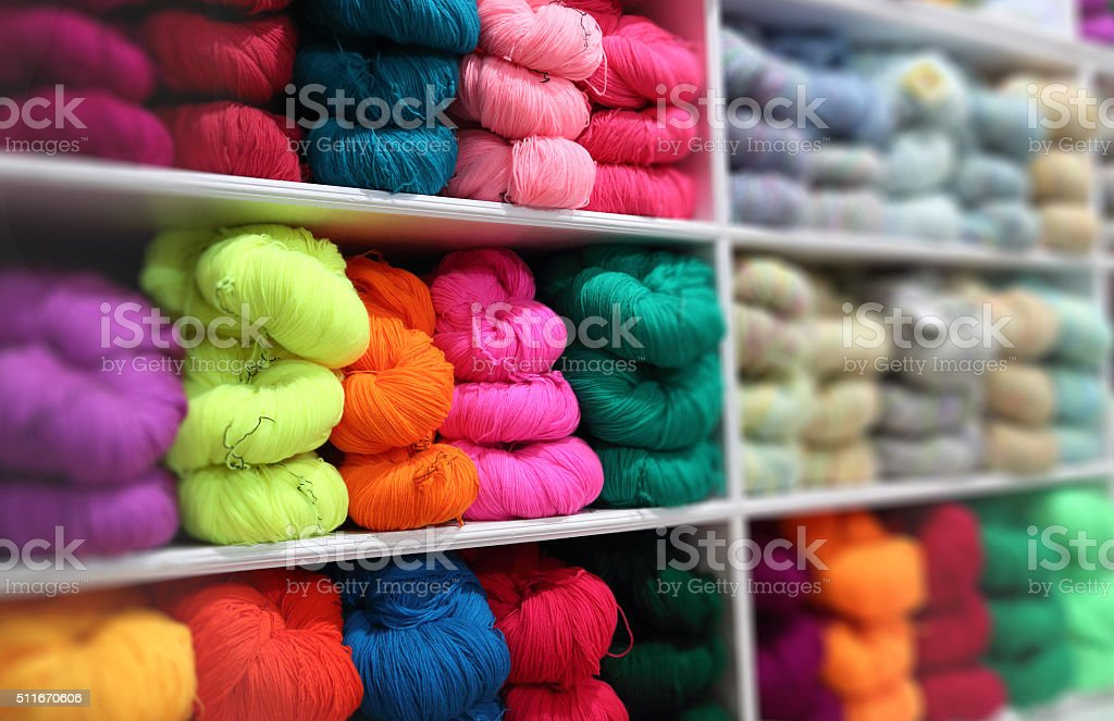 Various colors of wool in the shop stock photo