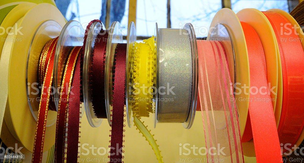 Various colors ribbon bobbins stand stock photo