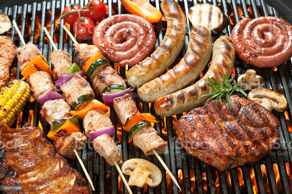 Various cooking meats on a flame grill stock photo