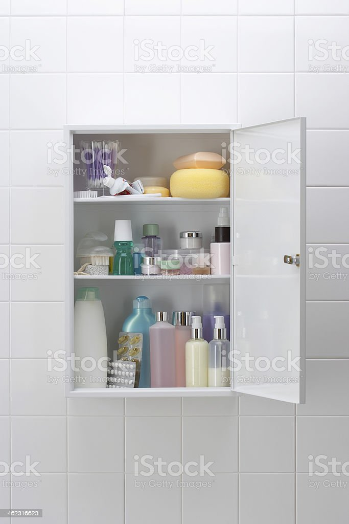 Various cosmetics and bath products in bathroom cabinet stock photo
