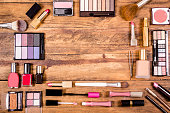 Various cosmetics, make-up lie on wooden dressing table. Knolling.