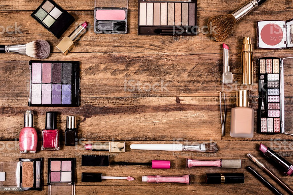 Various cosmetics, make-up lie on wooden dressing table. stock photo