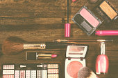 Various cosmetics, make-up lie on wooden dressing table.