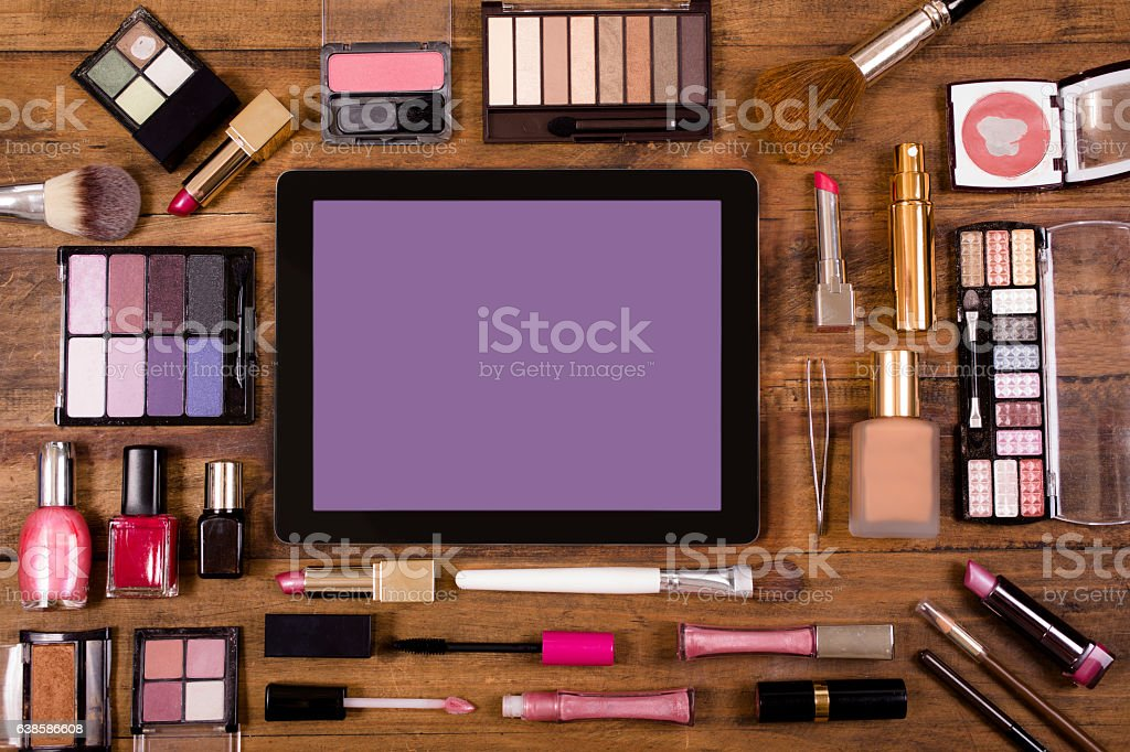 Various cosmetics surround a digital tablet on dressing table. stock photo