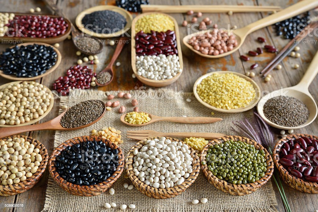 Various dried legumes in wooden untelsil stock photo