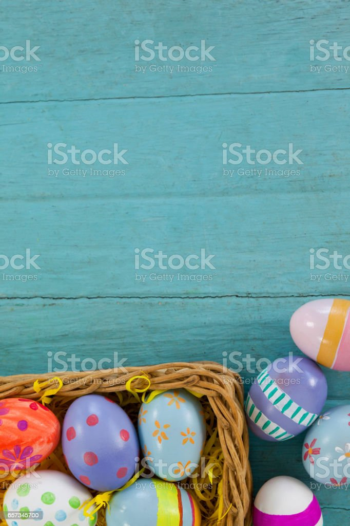 Various Easter eggs arranged in wicker basket stock photo