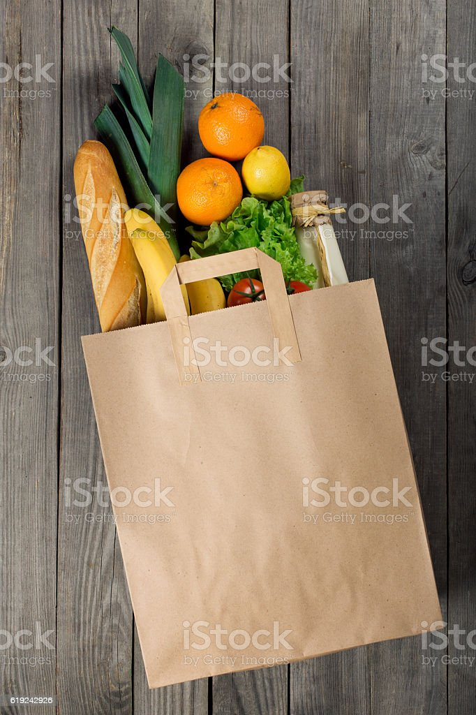 Various food in paper bag on wooden background stock photo