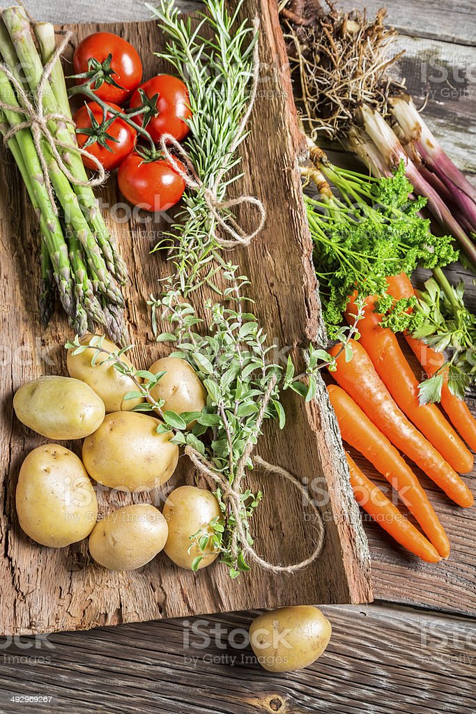 Various fresh vegetables on bark stock photo