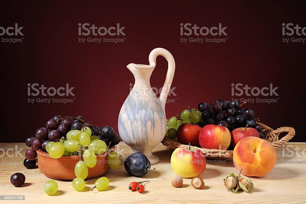 Various fruits and a ceramic jug stock photo