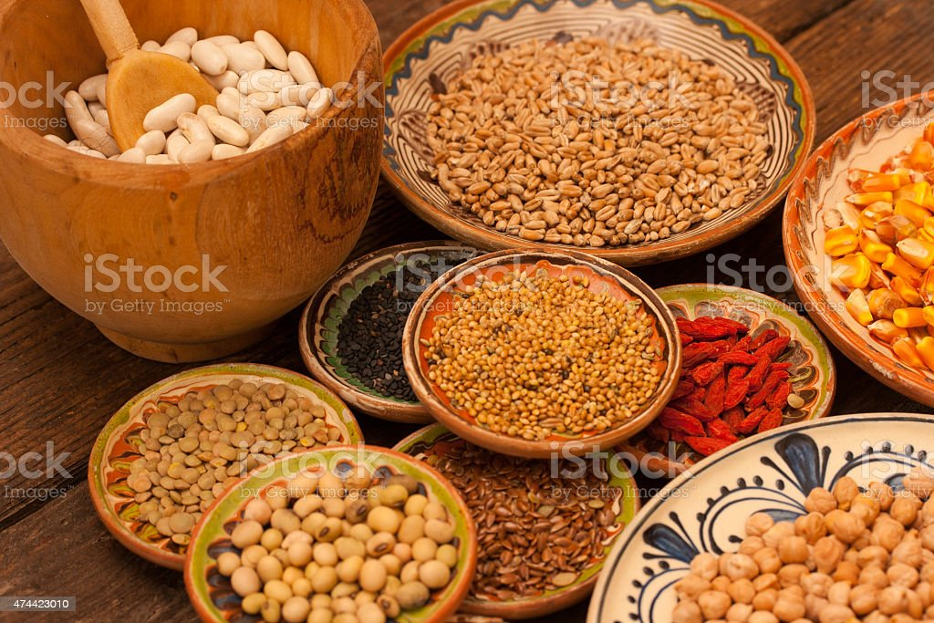 Various grain beans in small clay plates on wood background stock photo
