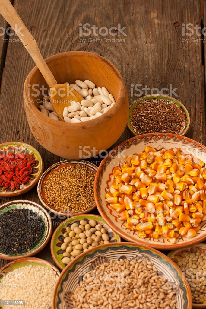 Varios granos de cereales en pequeñas clay placas en fondo de madera foto de stock libre de derechos