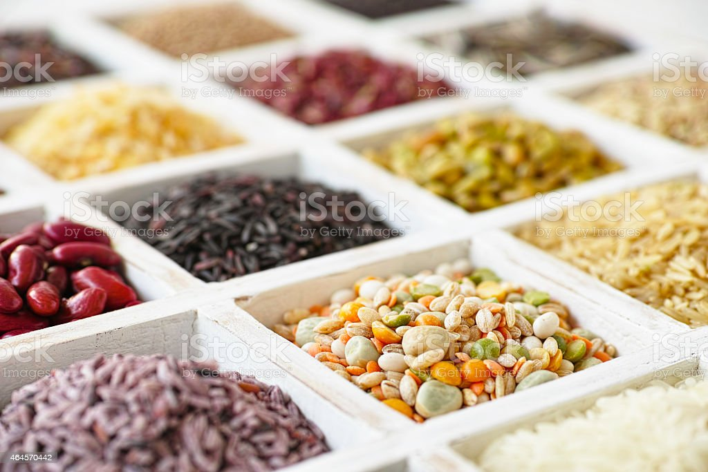 Various grains, beans, pulses, nuts and seeds in a tray. stock photo