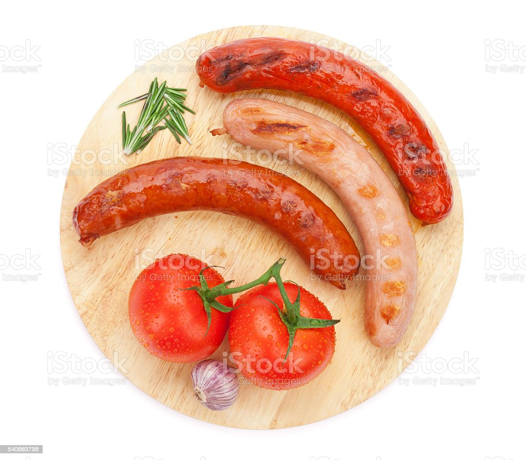 Various grilled sausages with condiments and tomatoes stock photo