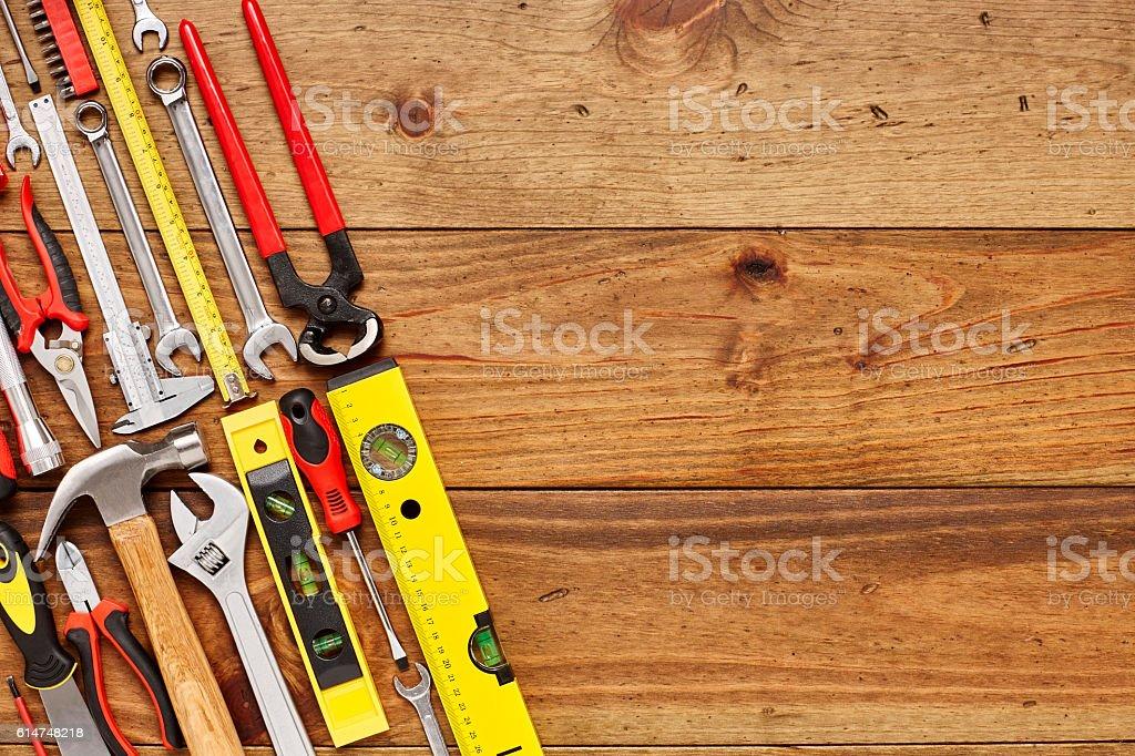 Various hand tools diagonally arranged on wooden floor stock photo