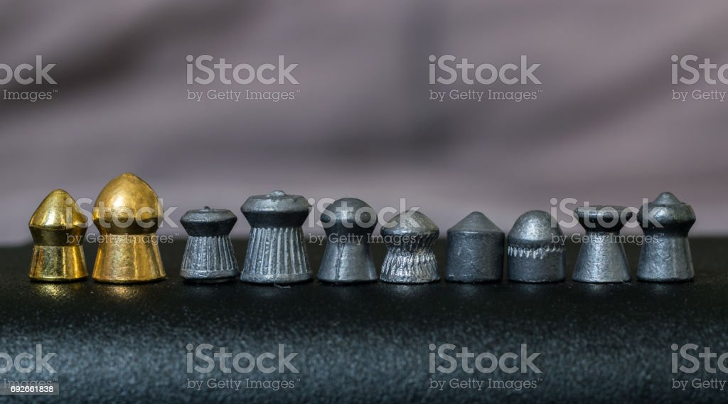 Various kinds of airgun pellets in a line stock photo