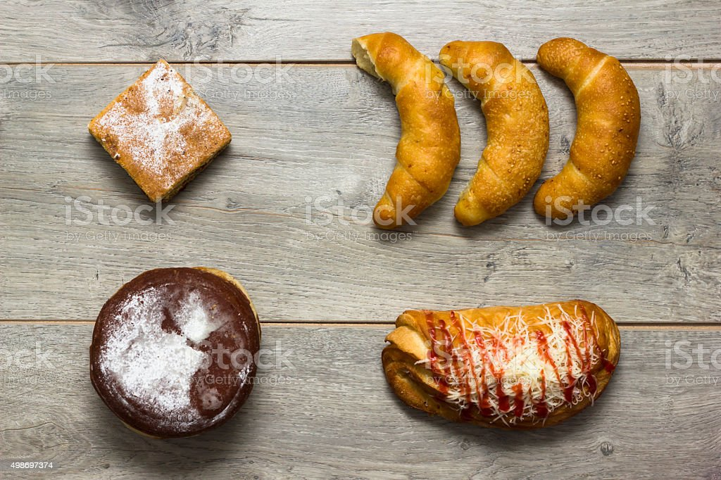Various kinds of baked products on wooden textured table stock photo
