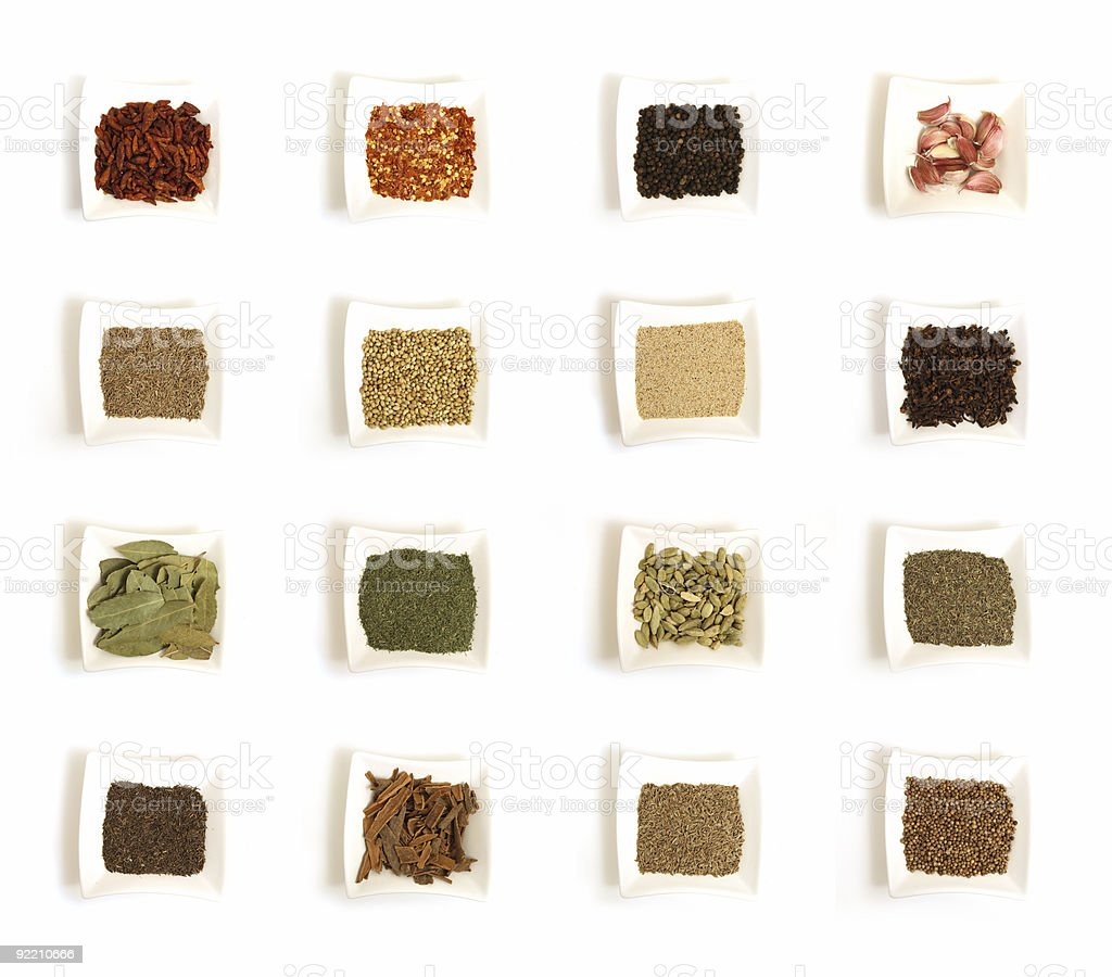 Various kinds of spices in sixteen white square bowls royalty-free stock photo