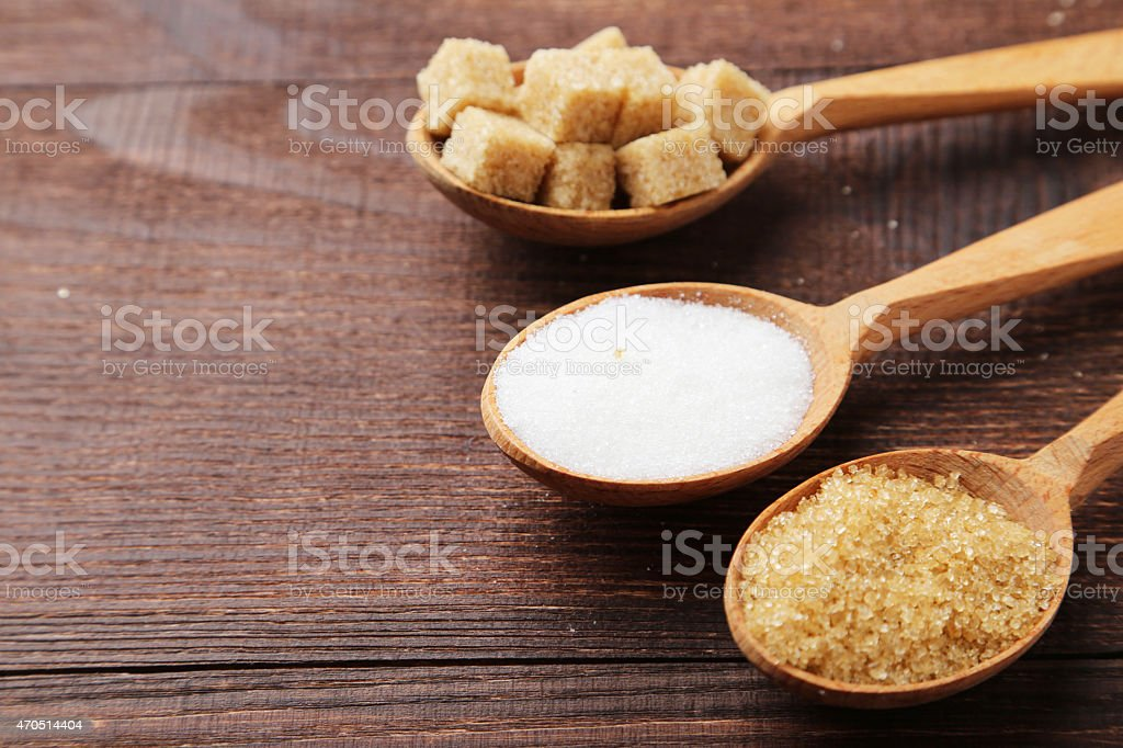 Various kinds of sugar in spoons on brown wooden background stock photo