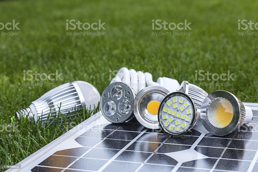 various LED lamps on photovoltaic cells and CFL in grass royalty-free stock photo