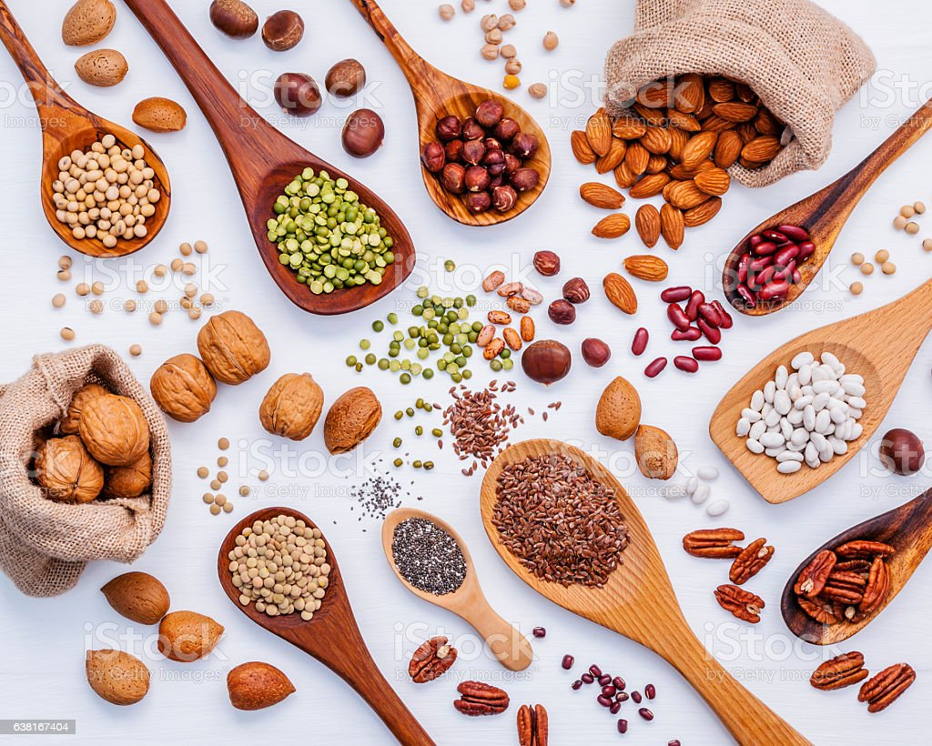 Various legumes and different kinds of nuts in spoons. Walnuts stock photo