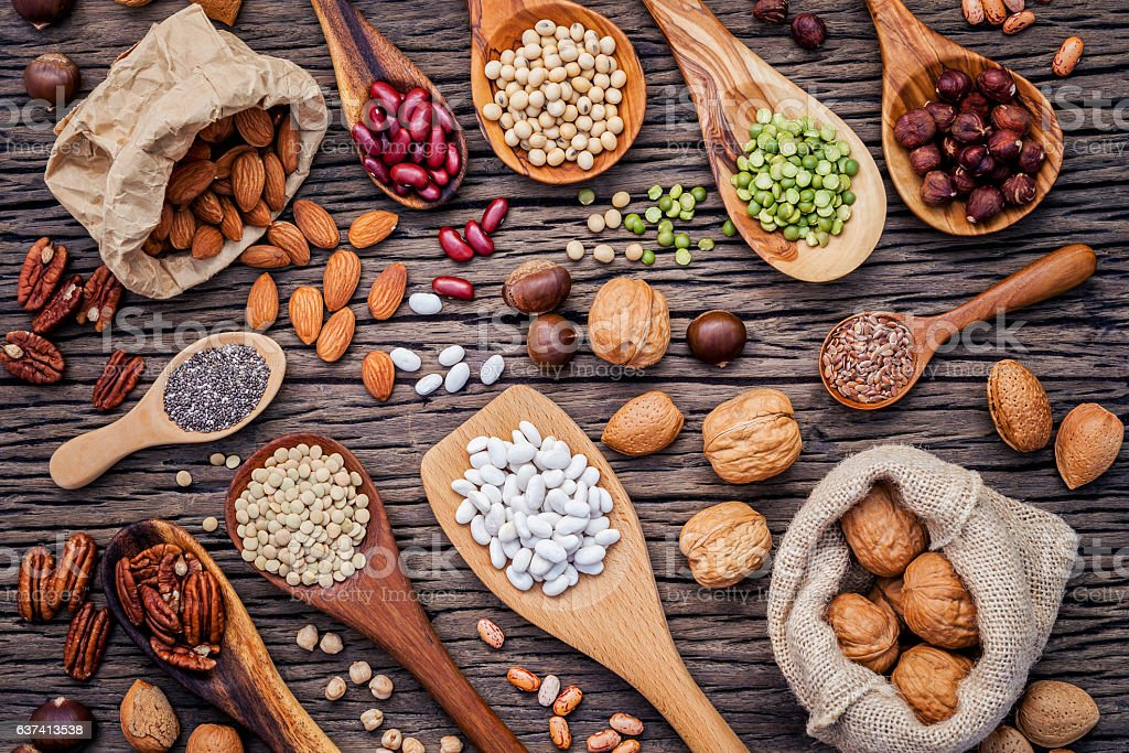 Various legumes and different kinds of nutshells in spoons. Waln stock photo