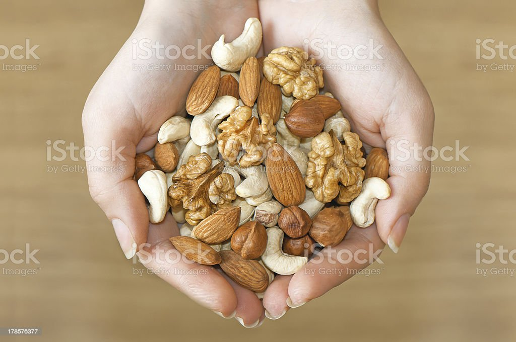 Various nuts in hands stock photo