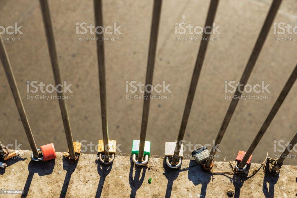 Various padlocks with drawn hearts tied on a bridge stock photo