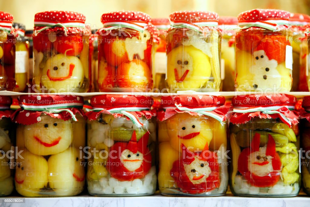 Various pickled vegetables in glass jars on retail market for sale stock photo