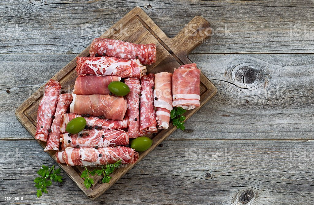 Various raw meats on rustic serving board stock photo