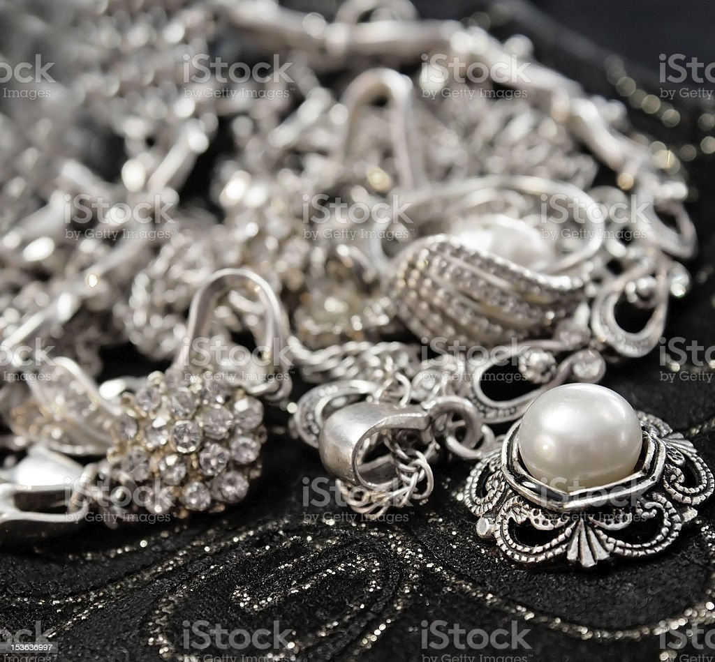 Various silver shining jewellery and closeup pearl on black stock photo