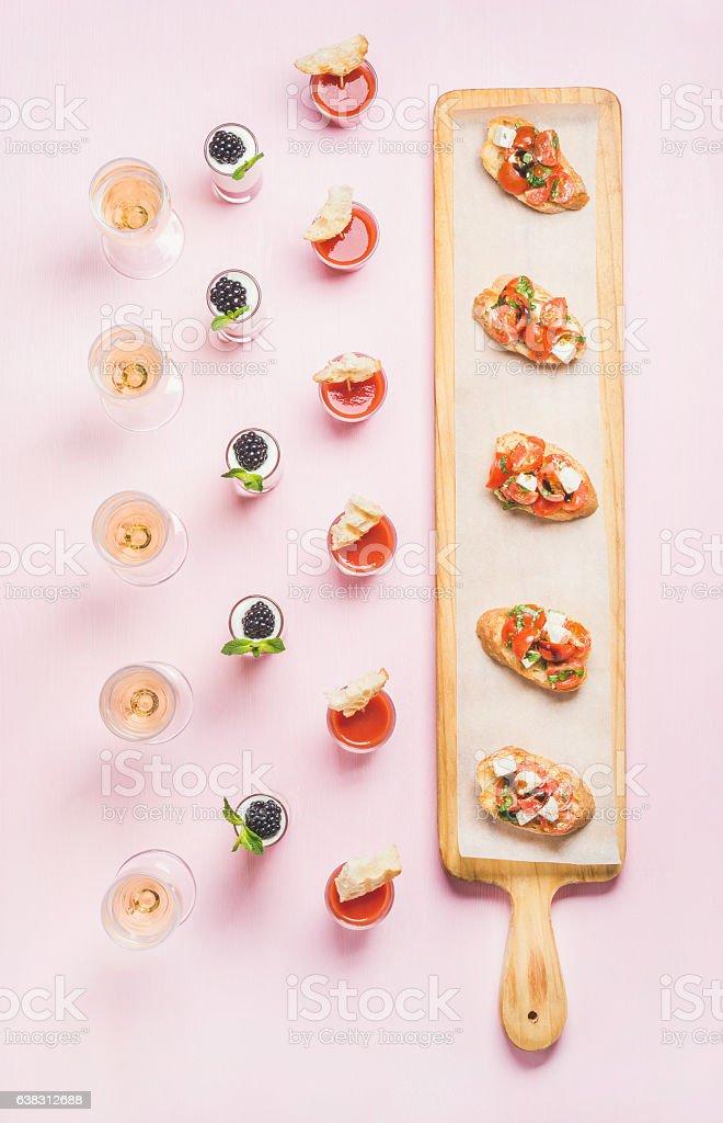 Various snacks, brushetta sandwiches, gazpacho shots, desserts over pink background stock photo