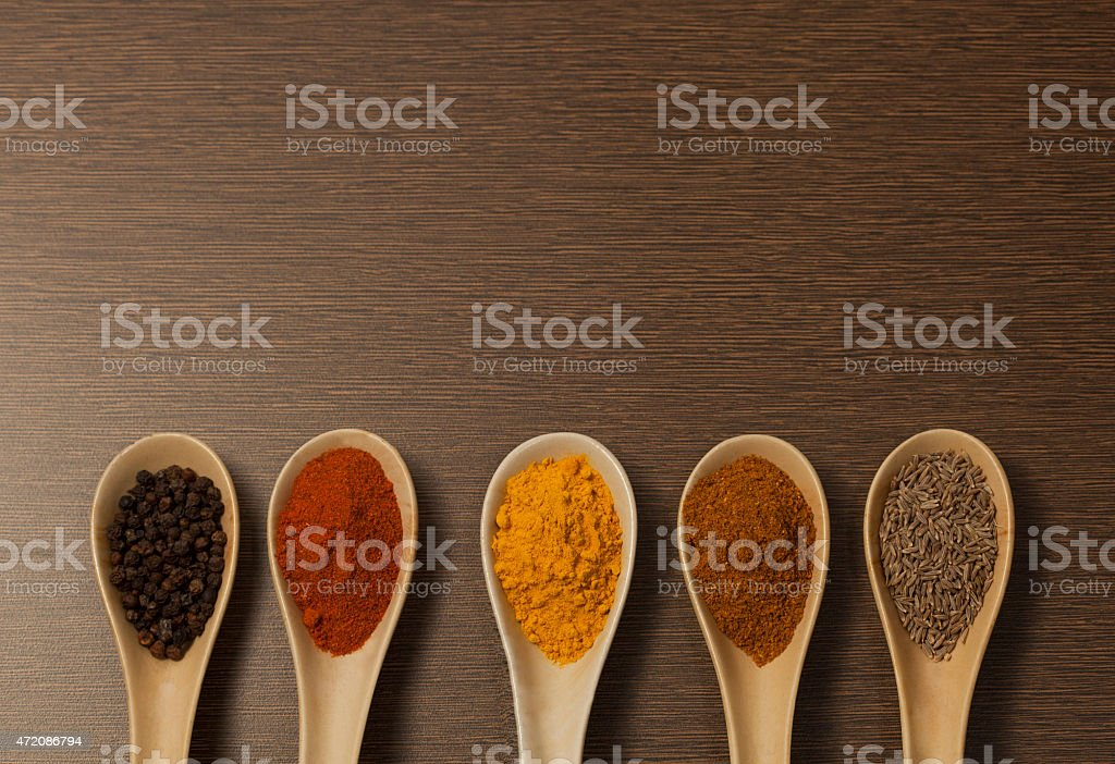 Various spices in ceramic spoon on wooden backgound stock photo