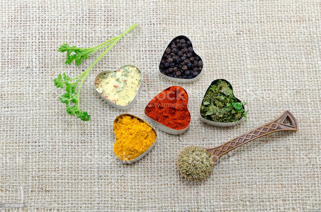 Various spices in heart chaped containers and a spoon royalty-free stock photo