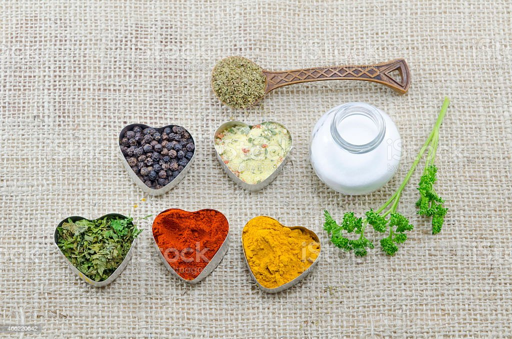 Various spices in heart chaped containers with salt and spoon royalty-free stock photo