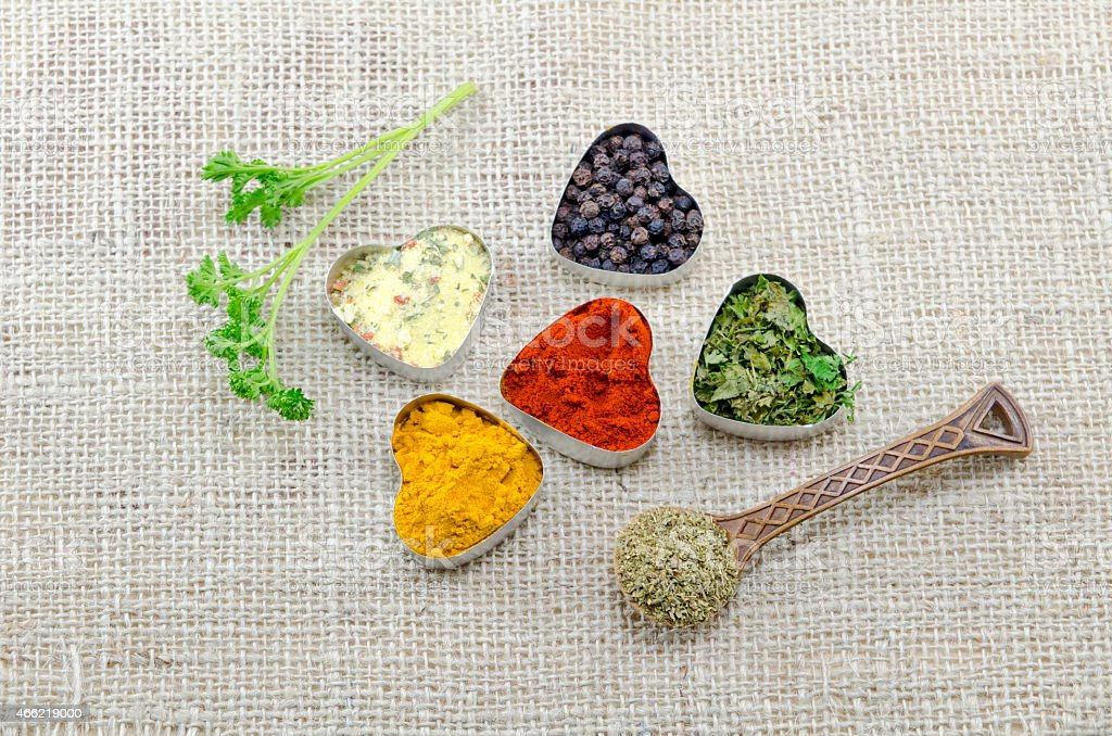Various spices in heart shaped containers and a spoon royalty-free stock photo
