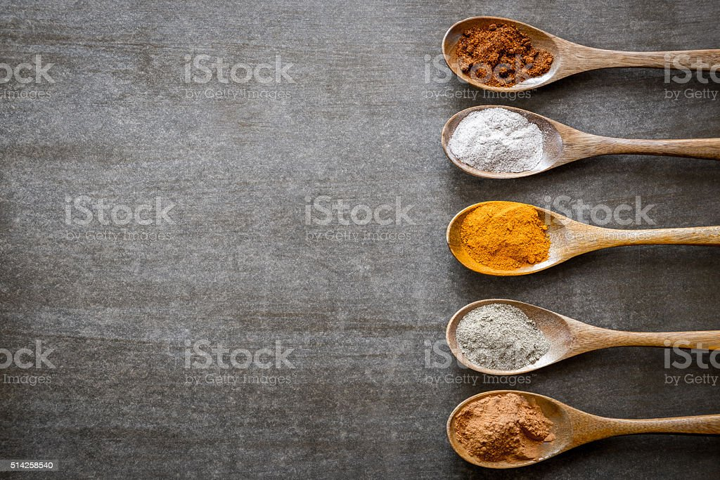 Various spices on wooden spoons stock photo