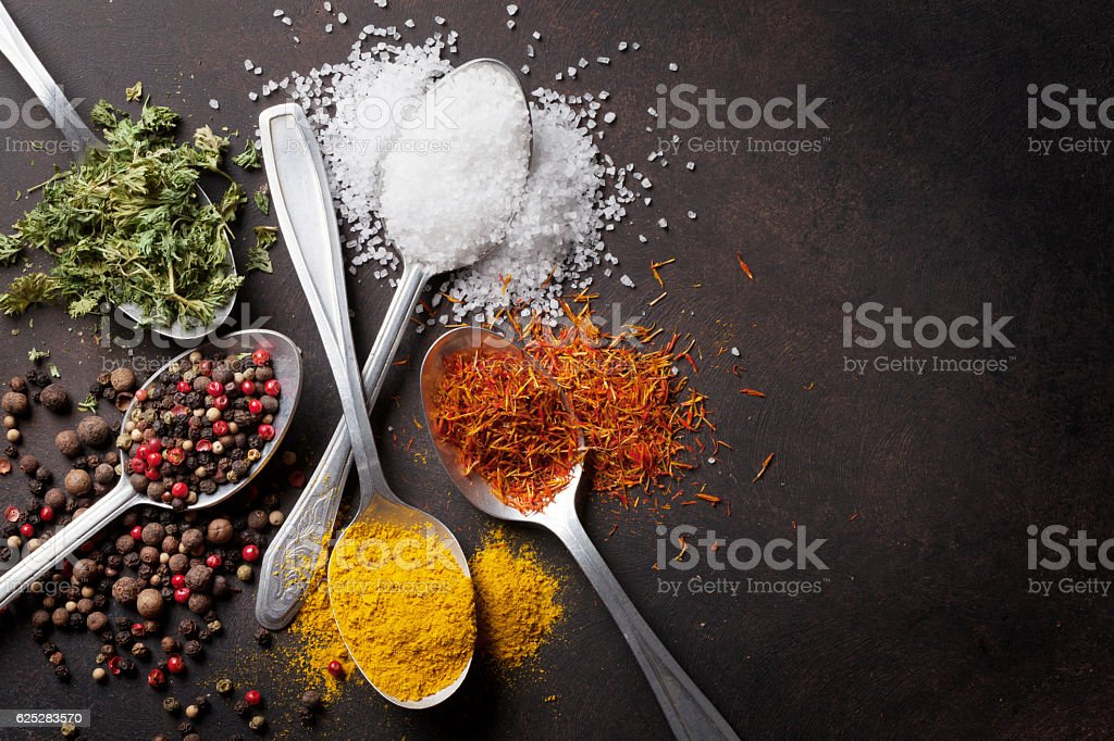 Various spices spoons on stone table stock photo