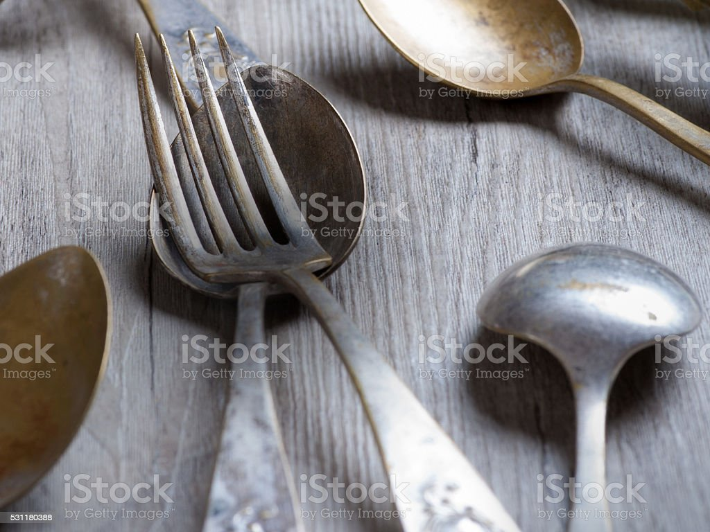 various spoons and forks entwined on rustic wooden table stock photo