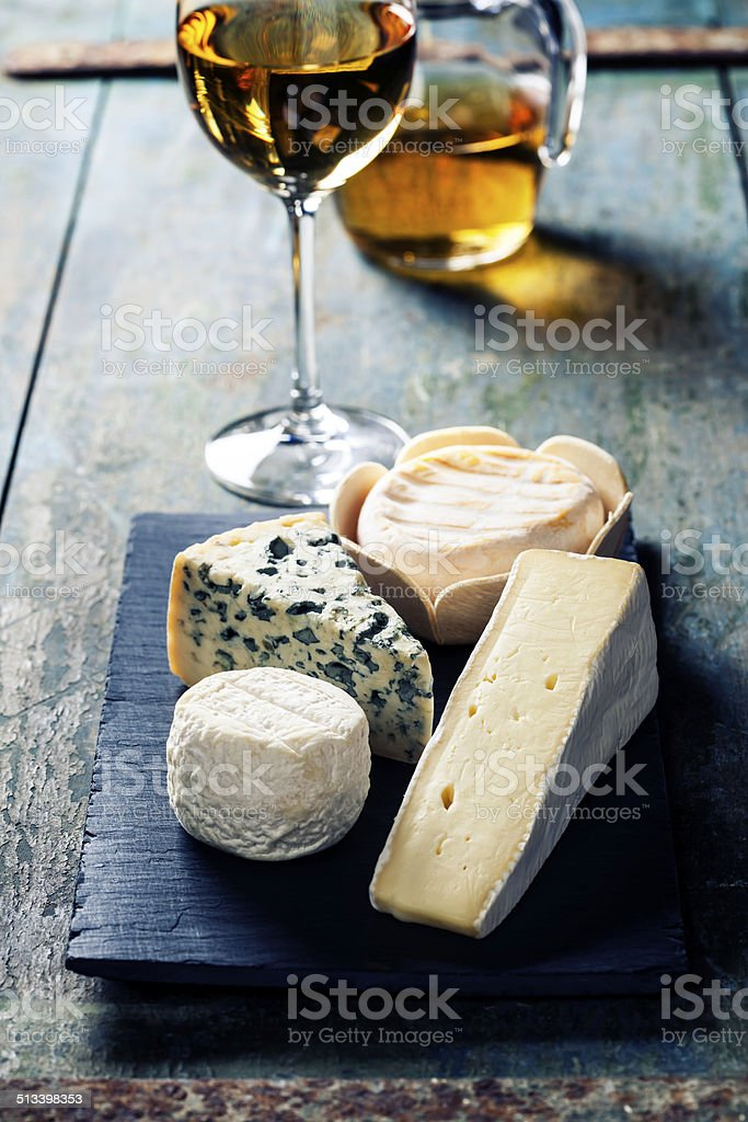 Various types of cheese and white wine stock photo