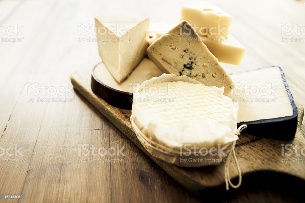 Various types of cheese on a wooden board stock photo