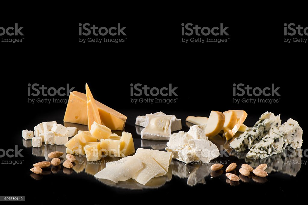 Various types of cheese over black with reflection stock photo