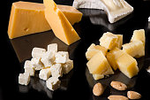 Various types of cheese over black with reflection
