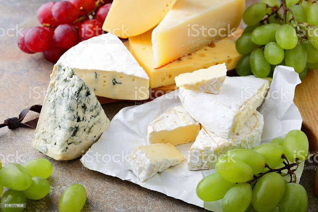 Various types of Cheese with grapes on slate stock photo
