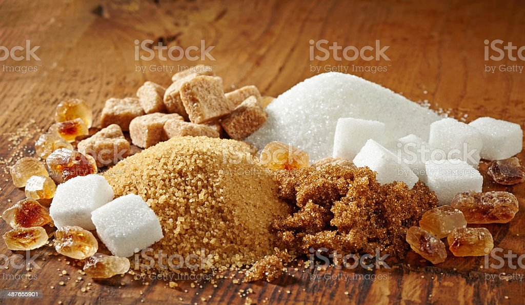 various types of sugar on wooden table stock photo