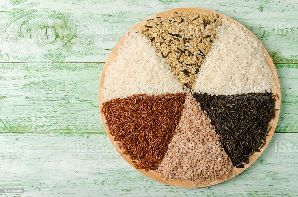 Various varieties of rice on a wooden table stock photo