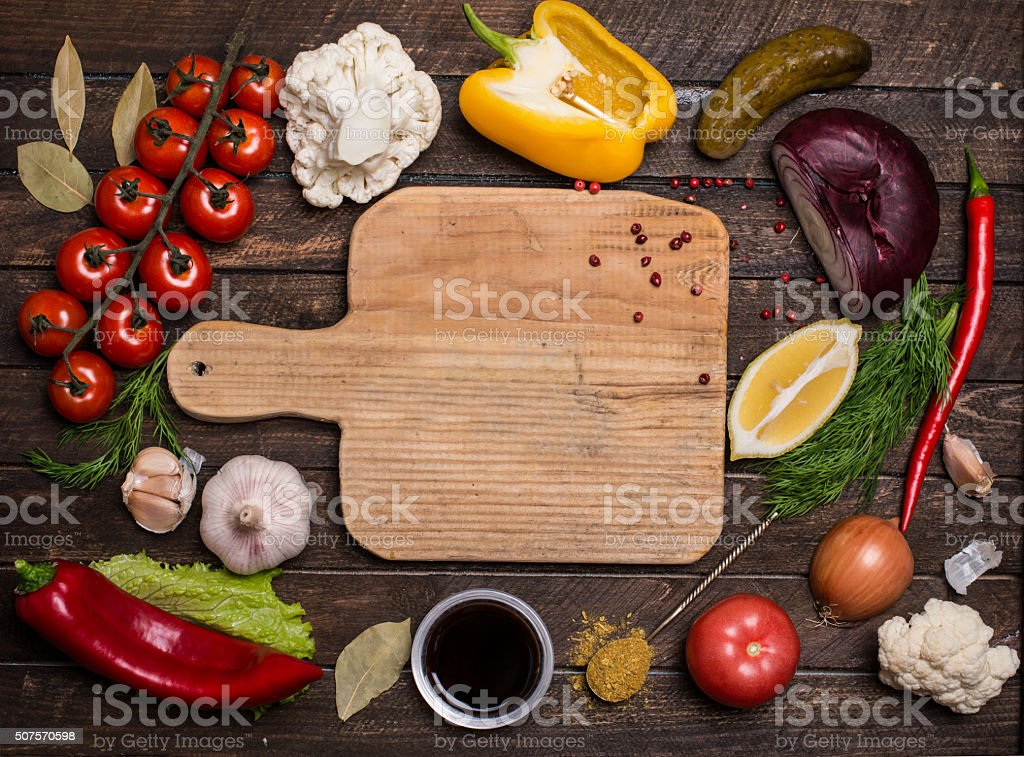 Various vegetables and spices and empty old cutting board. stock photo