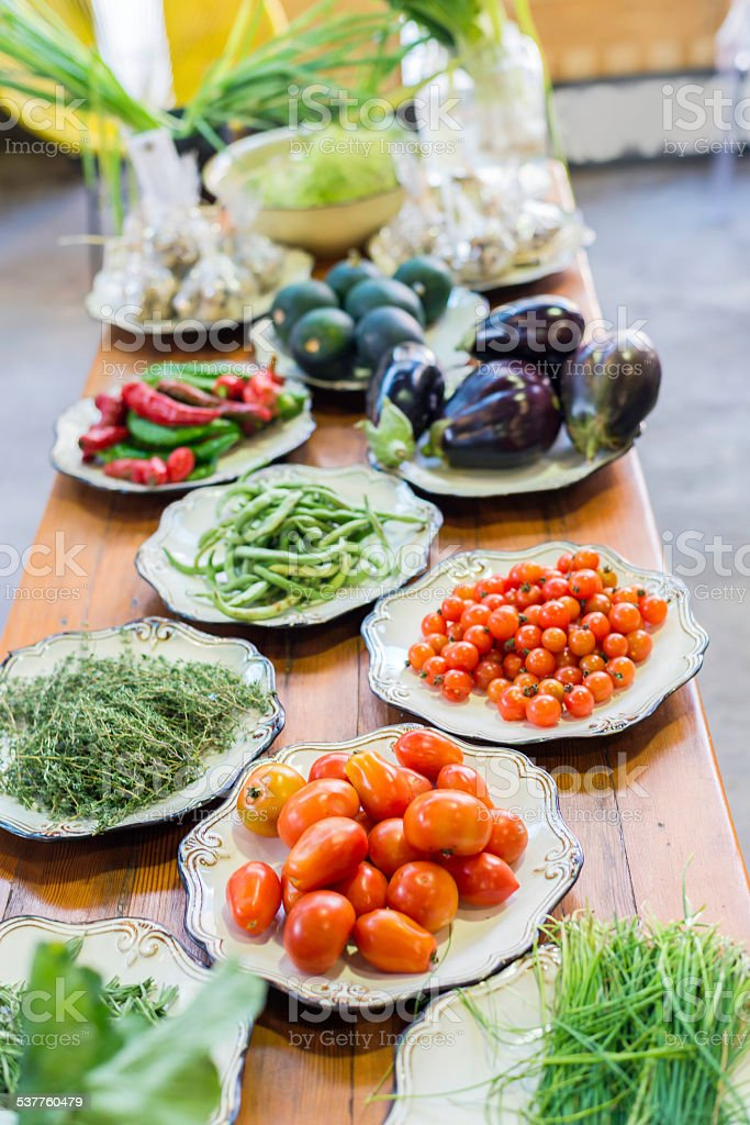 Various vegetables on a table, displayed on plates stock photo